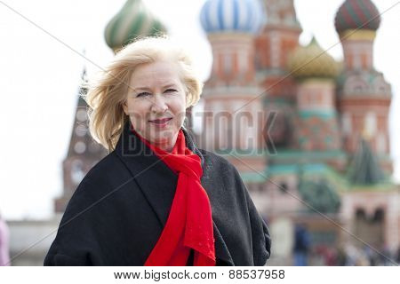 Happy portrait of an elderly blonde woman, against the background of the Red Square, Moscow, Russia