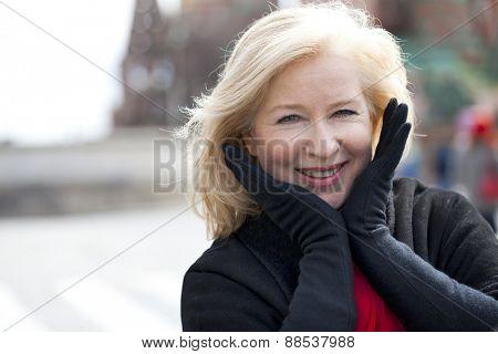 Happy portrait of an elderly blonde woman, spring on the street