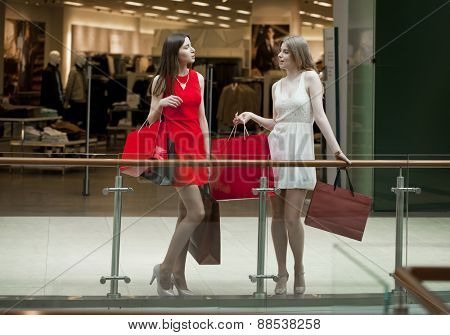 Two happy girlfriends on shopping walk on shopping centre with bags