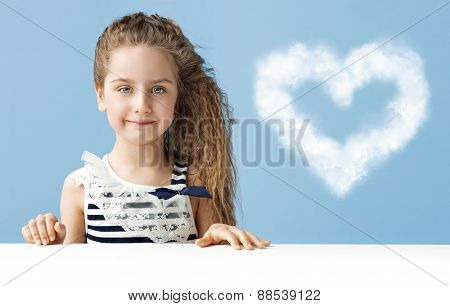 Little girl with heart-shaped cloud