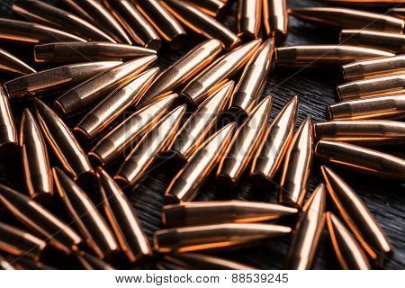 Placer copper bullets on a dark wooden background