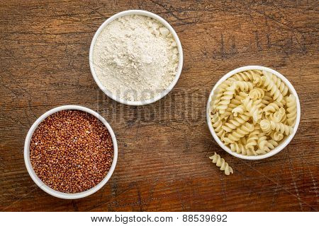 gluten free quinoa grain, flour and pasta - top view of small ceramic bowls against rustic wood