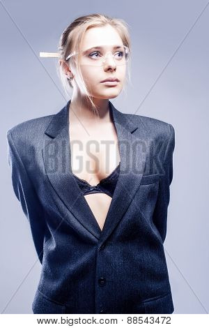 Fashion Concept: Portrait Of Sexy Caucasian Blond Model Dressed In Gray Suite And Posing Against Gra
