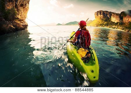 Young lady paddling the kayak in a calm bay with limestone mountains