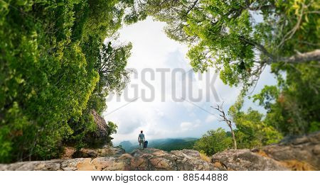 Hiker with backpack standing on the rock surrounded by lush tropical forest. Edges of image are blurred