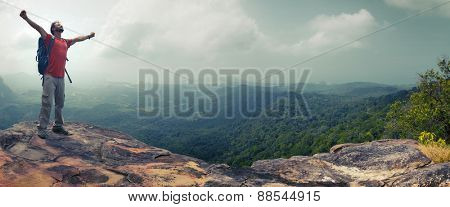 Hiker with backpack standing on top of the mountain at sunny day