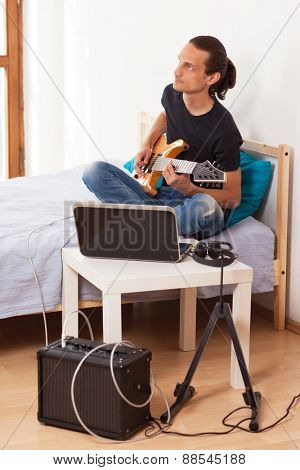 Young man playing electric guitar at home.