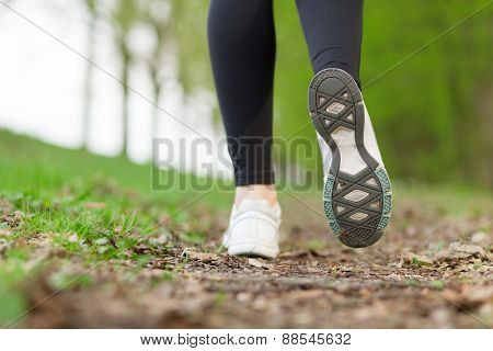Feet of a running woman in the forest
