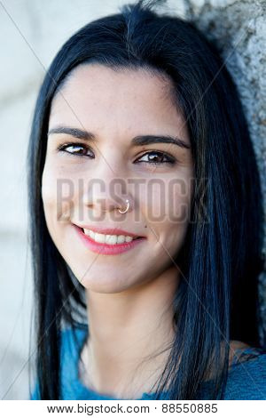 Portrait of brunette cool girl with a piercing in her nose