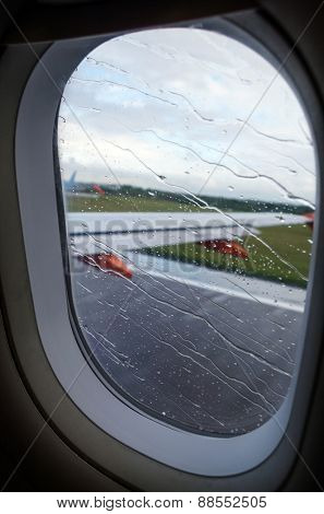 View of rainy airplane window during takeoff