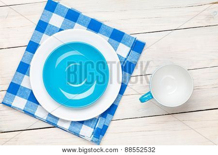 Empty plate, cup and towel over wooden table background. View from above with copy space