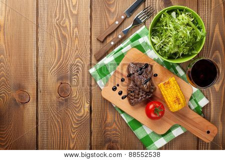 Steak with grilled corn, salad and red wine on wooden table. Top view with copy space