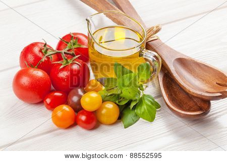 Fresh colorful tomatoes, basil and olive oil on white wooden table