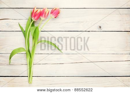 Colorful tulips on wooden table. Top view with copy space. Toned