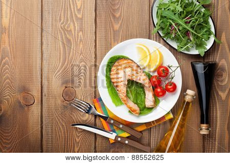 Grilled salmon, salad and condiments on wooden table. Top view with copy space