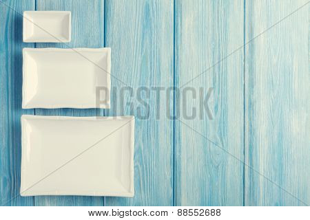 Empty plates and bowls on blue wooden background. Retro toned. Top view with copy space