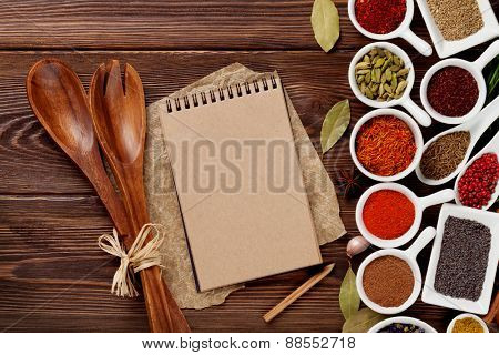 Various spices on wooden background. Top view with notepad for copy space