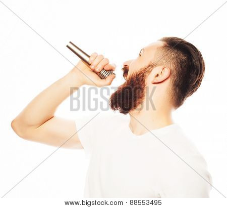 Life style concept: a young man with a beard wearing a white shirt holding a microphone and singing.Isolated on white.