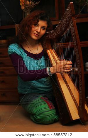 Young Woman Playing Celtic Harp In A Ethno Costume.