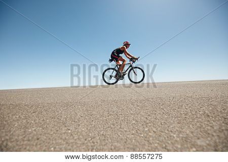 Female Cyclist On A Country Road Training For Triathlon
