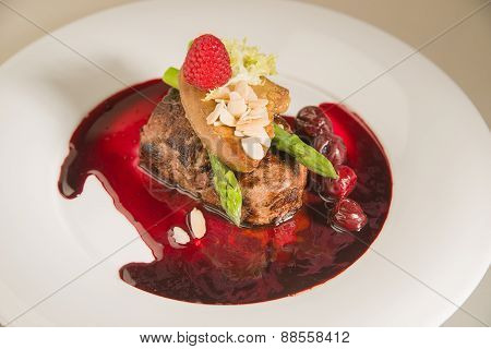 Piece Of Roasted Meat In Cherry Sauce, Asparagus  And Raspberry  On A White Plate