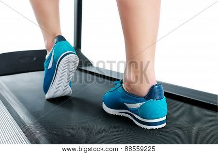Female Legs In Turquoise Sneakers On A Treadmill
