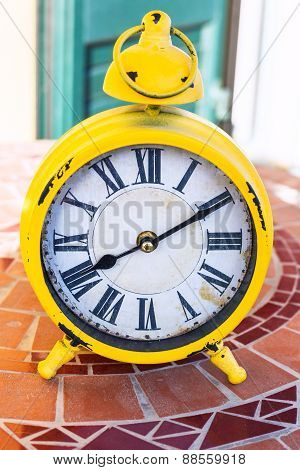 Old Yellow Mechanical Alarm Clock On Stone Table