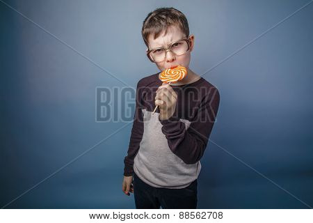 boy teenager European appearance in sunglasses licks candy color