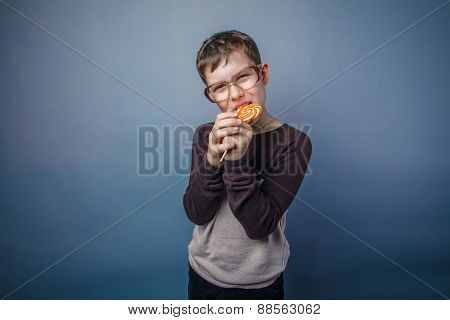 boy teenager European appearance in sunglasses nibbles candy col