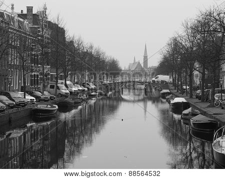 Boat lined canal with church at a cloudy but calm day in Leiden