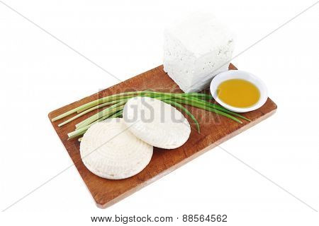 diet food : greek feta white cheese served on small wooden plate with olive oil isolated over white background