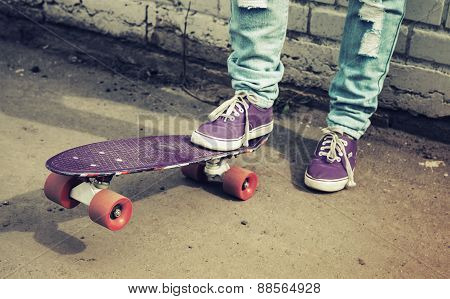 Teenager Feet In Jeans And Gumshoes With Skateboard