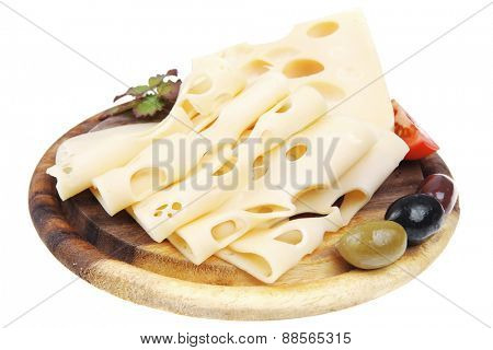 yellow edam cheese sliced on wooden platter with olives and tomato isolated over white background