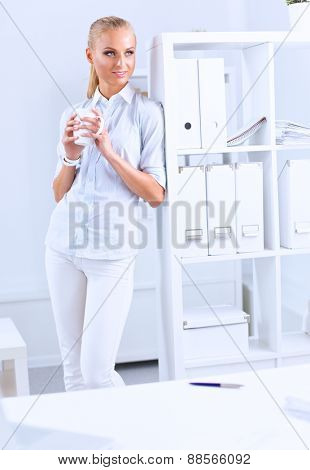 Young businesswoman standing near the desk with cup .