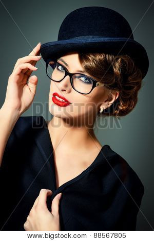 Beautiful woman wearing glasses and bowler hat. Retro style. Beauty, fashion. Make-up. Optics, eyewear.