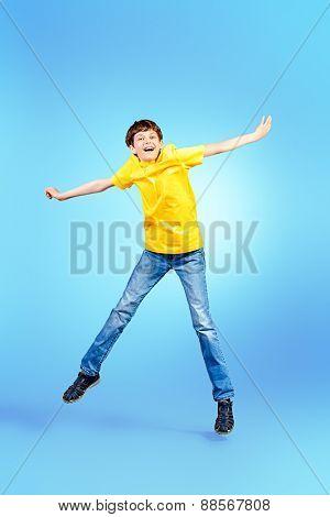 Full length portrait of a happy jumping boy. Success. Studio shot.