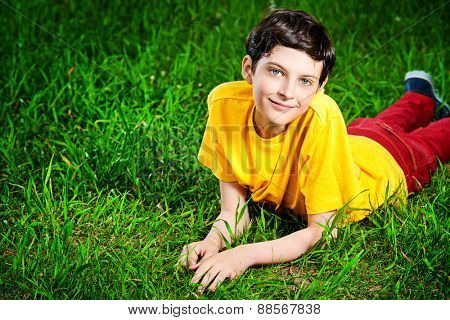 Smiling boy lying on a grass at a park. Summer day.
