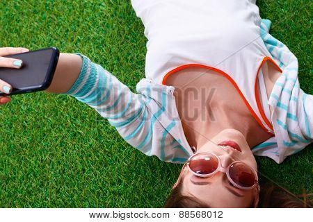 Beautiful young woman making selfie by her phone while lying in green grass.