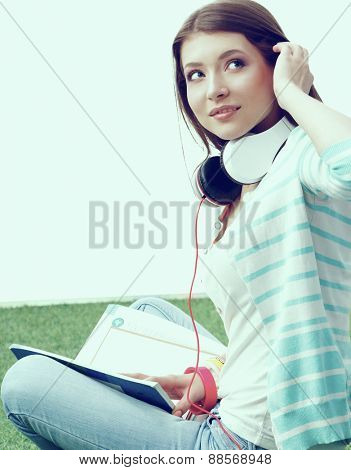 Woman reading book sits on the green grass.