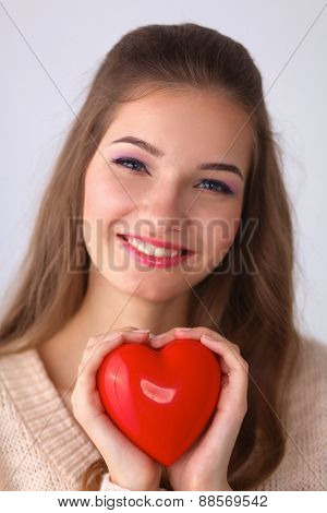 Portrait of beautiful happy woman holding a Valentine day symbol.