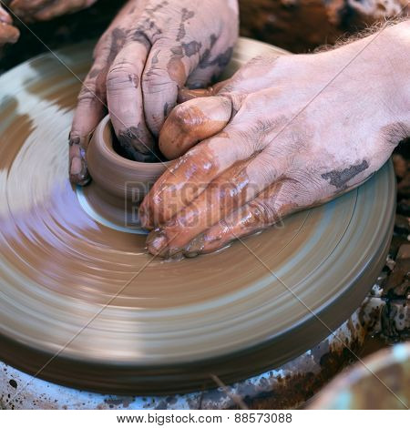 Hands working with clay on pottery wheel