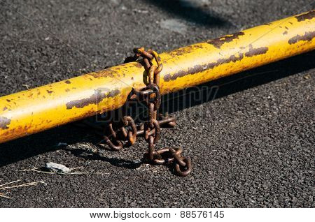 Rusty Chain With Old Yellow Security Bar