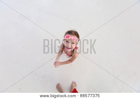 Top view of adorable little girl at beach during summer vacation