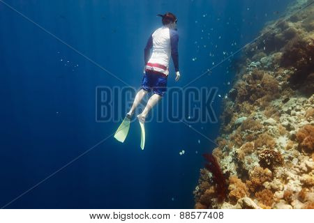 Underwater photo of a young man free diving at coral reef in tropical ocean