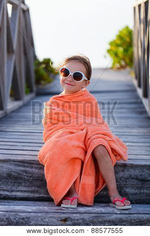 Cute little girl at beach covered with towel