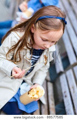 Adorable little girl enjoying eating take away food for lunch outdoors