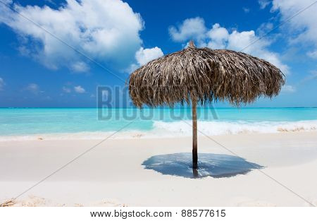 Tropical thatch umbrella on a beautiful Caribbean beach in Cuba