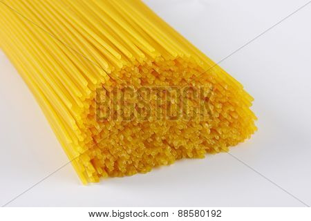 close up of uncooked spaghetti on white background