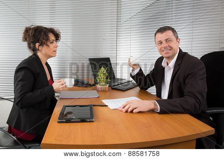 Man And Woman Talking Together Looking At Document