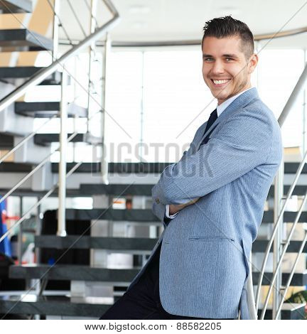 Portrait of positive business man standing on stairs of modern office